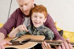 kantjusterat skott av fadern som undervisar den lyckliga sonen som spelar gitarren royaltyfria bilder