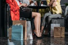 kantjusterat skott av kvinnor med att sitta för shoppingpåsar arkivfoton