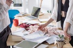 kantjusterat skott av modeformgivare som tillsammans arbetar på arbetsplatsen royaltyfria foton