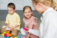 kantjusterat skott av modern som ser gulliga små ungar som spelar med färgrika kvarter royaltyfri bild