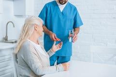 kantjusterat skott av sjukskötaren som ger exponeringsglas av vatten och piller till pensionären fotografering för bildbyråer