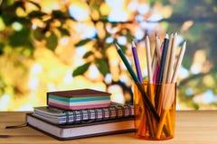 Kantoorbehoeften, blocnote, adresboek, nota's, potloden in een glas op een houten lijst stock foto's