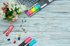 Kantoorbehoeften, bloemen en laptop Stock Afbeelding