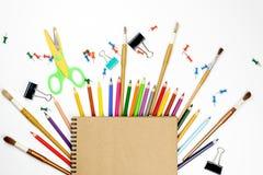 Kantoorbehoeften kleurrijke die het schrijven de pennenpotloden van hulpmiddelentoebehoren, Kraftpapier-document op witte achterg royalty-vrije stock foto's