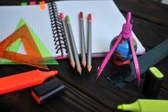 Kantoorbehoeften met een bol op een notitieboekje uit wordt uitgespreid die op een donkere houten lijst liggen die royalty-vrije stock afbeeldingen