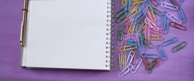 Kantoorbehoeften, paperclippen, blocnote en pen voor bureau of school royalty-vrije stock afbeeldingen