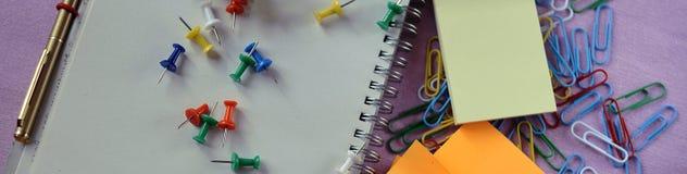 Kantoorbehoeften, paperclippen, blocnote en pen voor bureau of school royalty-vrije stock foto