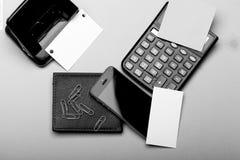 Kantoorbehoeften, portefeuille, telefoon en calculator Adreskaartjes met exemplaarruimte en klemmen met stickers stock fotografie