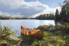 Kanu auf dem Ufer von einem Nordminnesota See während des Herbstes lizenzfreies stockfoto