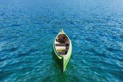 Kanu, das auf das transparente Meerwasser schwimmt Lizenzfreie Stockbilder
