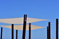 Kanwa cienie na czarnych słupach przeciw niebieskiemu niebu obraz stock
