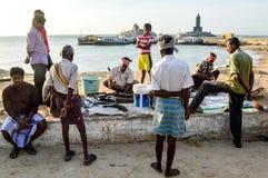 Kanyakumari Tamil Nadu, Indien 08/14/14 En man som säljer fisken på kanten av stranden som folk, ser på, med statyn av Viveka Arkivfoton