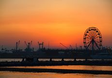 Kaohsiung Harbor at Dusk. View of Kaohsiung Harbor at sunset with the silhouette of a small ferris wheel Stock Images