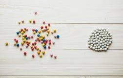 Kaotiska färgrika bollar och organiserade vita bollar Begreppsmässigt av Royaltyfria Bilder