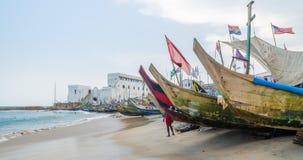 Kap-Küste, Ghana - 15. Februar 2014: Bunte festgemachte hölzerne Fischerboote im afrikanischen Hafenstadtkap fahren die Küste ent Lizenzfreies Stockbild
