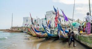 Kap-Küste, Ghana - 15. Februar 2014: Bunte festgemachte hölzerne Fischerboote im afrikanischen Hafenstadtkap fahren die Küste ent Lizenzfreie Stockfotografie