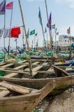 Kap-Küste, Ghana - 15. Februar 2014: Bunte festgemachte hölzerne Fischerboote im afrikanischen Hafenstadtkap fahren die Küste ent Lizenzfreie Stockfotos