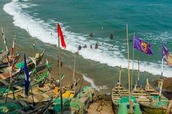 Kap-Küste, Ghana - 15. Februar 2014: Bunte hölzerne Fischerboote in der afrikanischen Stadtkap-Küste und schwimmende Einheimische Stockfoto