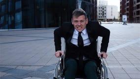 Kapabel krymplingman som försöker att få upp från rullstolen arkivfilmer