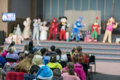 Kapacitet för barn på etapp Barn på etapp utför framme av föräldrar bild av suddighetsunges show på etapp på skola, royaltyfria bilder