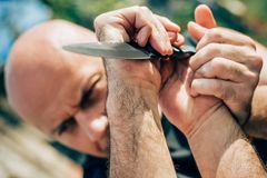 Kapap instructor demonstrates martial arts self defense knife at. Tack disarming technique against threat and knife attack. Weapon retention and disarm training stock image