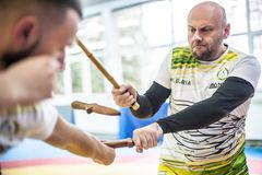 Kapap instructor Igor Sucevic teaches stick knife together fighting techniques. PLOVDIV, BULGARIA - 15. DECEMBER 2018. Stick and knife together fighting royalty free stock photo
