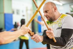 Kapap instructor Igor Sucevic teaches stick knife together fighting techniques. PLOVDIV, BULGARIA - 15. DECEMBER 2018. Stick and knife together fighting stock image