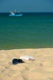 Kapcie i ręcznik na prostej dzikiej plaży obrazy stock