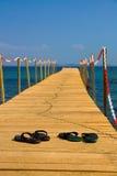 Kapcie na drewnianym rówieśniku z błękitnym morzem Obrazy Royalty Free