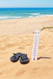 Kapcie na plaży obok termometru i morza. Obrazy Stock