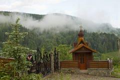 Kapel in de bergen op de achtergrond van beboste hellingen Royalty-vrije Stock Foto's