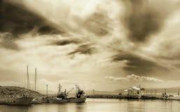 Kapel en vissersboten onder een dramatische hemel in haven royalty-vrije stock foto