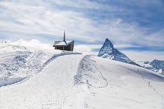 Kapel op de sneeuwberg met de achtergrond van Matterhorn Stock Foto's