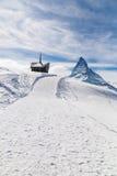 Kapell på snöberget med bakgrunden av Matterhorn Arkivfoto