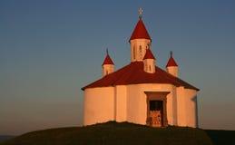 Kapelle auf dem Hügel im Sonnenuntergang Stockfotografie