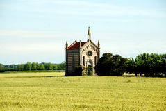 Kapelle auf einem Maisgebiet nahe bei Bäumen nähern sich comacchio in Italien Lizenzfreie Stockfotos