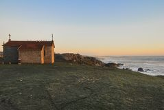 Kapelle, die den Ozean bei Sonnenuntergang übersieht stockbild