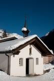 Kapelle unter dem Schnee in den Bergen Lizenzfreies Stockfoto