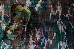 Kapelusz na militarnym kamuflaż sieci tle Fotografia Stock