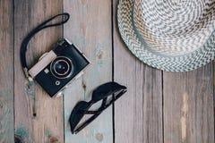 Kapelusz, stara kamera i okulary przeciwsłoneczni na drewnianym stole, zdjęcia royalty free