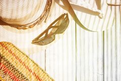 Kapeluszowe, białe trzepnięcie klapy, okulary przeciwsłoneczni, plażowa torba na białym drewnianym tle, ciężki światło fotografia royalty free