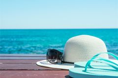 Kapeluszowi okularów przeciwsłonecznych kapcie na niebieskiego nieba i turkusu morza tle Wakacje podróży relaks idylliczny seasca obraz stock