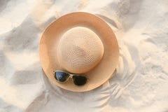 kapeluszowy lato - słomianego kapeluszu fasion i okularów przeciwsłonecznych akcesoria na piaskowatej plaży dennego tła odgórnym  fotografia stock