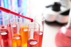 Kapiący odczynnik w próbną tubkę z próbką w chemii laboratorium, zbliżenie obraz stock