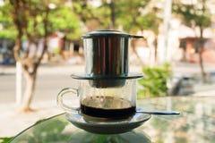 Kapie Czarną kawę w wietnamczyka stylu z zgęszczonym mlekiem na szklanym stole Obrazy Stock