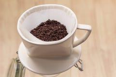 Kapinos kawa z papieru filtra narzędziem na drewnianym tle obraz royalty free