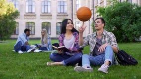 Kapitän des Basketball-Teams flirtend mit schönem biracial Studenten-Verhältnis stockfotos