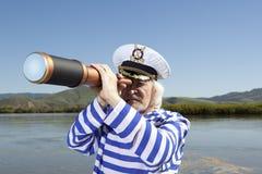 Kapitän schaut durch ein Teleskop lizenzfreie stockbilder