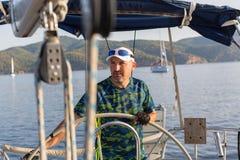 Kapitein bij het roer van zijn varend jacht Sport stock fotografie