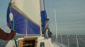 Kapitein die grootzeil op mooi jacht, het reizen opzetten stock video